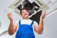 The worker repairing ceiling air conditioning unit. Worker repairing ceiling air conditioning unit Stock Images
