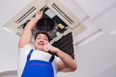 The worker repairing ceiling air conditioning unit. Worker repairing ceiling air conditioning unit Royalty Free Stock Photos