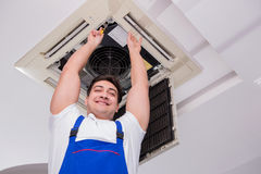 The worker repairing ceiling air conditioning unit. Worker repairing ceiling air conditioning unit Royalty Free Stock Image
