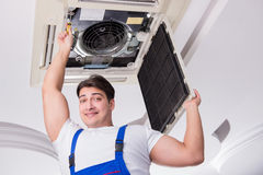 The worker repairing ceiling air conditioning unit. Worker repairing ceiling air conditioning unit Stock Photos