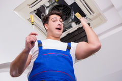 The worker repairing ceiling air conditioning unit. Worker repairing ceiling air conditioning unit Stock Photography