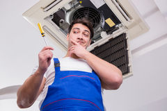 The worker repairing ceiling air conditioning unit. Worker repairing ceiling air conditioning unit Royalty Free Stock Photography