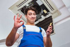 The worker repairing ceiling air conditioning unit Stock Photography