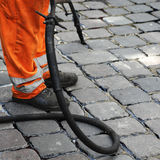 Worker repairing cobblestones. A closeup of a construction worker repairing cobblestones on a sidewalk or street Stock Photography