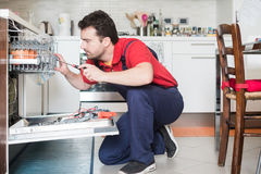 Worker repairing the dishwasher in the kitchen Stock Photo