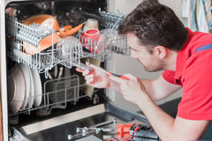 Worker repairing the dishwasher in the kitchen Stock Photography