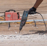 Worker repairing and drilling concrete road. Worker repairing and drilling the concrete road Royalty Free Stock Image