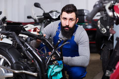 Worker repairing failed scooter in motorcycle garage. Positive man worker repairing failed scooter in motorcycle garage Stock Photos