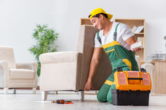 The worker repairing furniture at home Stock Image