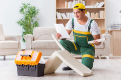 The worker repairing furniture at home Stock Photos