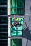 Worker repairing glass structure of high rise building royalty free stock photo