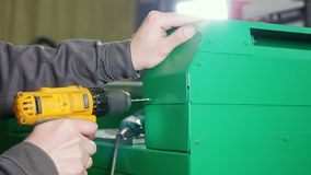 Worker repairing a machine at the factory using a hand drill. Industrial concept stock footage