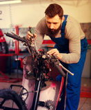 Worker repairing motorbike. Smiling male worker fixing failed motorcycle in motorcycle workshop Royalty Free Stock Photos