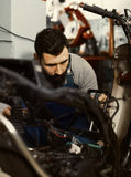 Worker repairing motorbike. Smiling male worker fixing failed motorcycle in motorcycle workshop Royalty Free Stock Photography