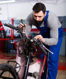 Worker repairing motorbike. Smiling male worker fixing failed motorcycle in motorcycle workshop Stock Photography