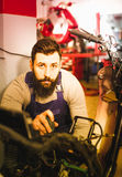 Worker repairing motorbike. Smiling male worker fixing failed motorcycle in motorcycle workshop Royalty Free Stock Images