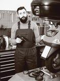 Worker repairing motorbike. Young male worker repairing motorbike in motorcycle workshop Royalty Free Stock Photo
