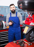 Worker repairing motorbike. Young male worker repairing motorbike in motorcycle workshop Stock Images