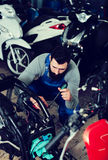 Worker repairing motorbike. Young male worker repairing motorbike in motorcycle workshop Royalty Free Stock Photography