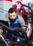Worker repairing motorbike. Young man worker working at restoring motorbike in motorcycle workshop Royalty Free Stock Images