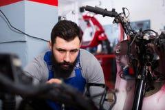 Worker repairing motorbike. Young man worker working at restoring motorbike in motorcycle workshop Stock Image