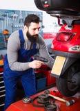Worker repairing in motorcycle workshop Stock Photography