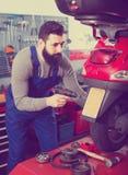 Worker repairing in motorcycle workshop. Young male worker using his tools for repairing in motorcycle workshop Royalty Free Stock Images