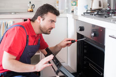 Worker repairing the oven in the kitchen Royalty Free Stock Images