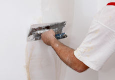 Worker repairing plaster to wall Stock Photo