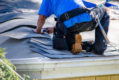Worker Repairing the roof of a home Stock Images