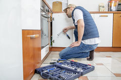 Worker repairing the sink in the kitchen. Man looks at the sink and holding a wrench. Next to the man lies toolbox Royalty Free Stock Image