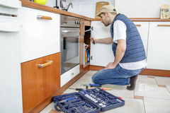Worker repairing the sink in the kitchen. Man looks at the sink and holding a wrench. Next to the man lies toolbox Royalty Free Stock Photography