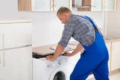 Worker Repairing Washer. Young Worker With Toolbox Repairing Washer In Kitchen Room Royalty Free Stock Images