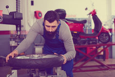 Worker repairing wheel. Smiling male worker fixing failed wheel in motorcycle workshop Stock Photography