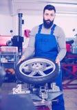 Worker repairing wheel. Young male worker repairing motorbike wheel in motorcycle workshop Royalty Free Stock Photography