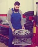 Worker repairing wheel. Young man worker working at restoring wheel in motorcycle workshop Stock Images