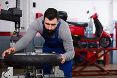 Worker repairing wheel. Young man worker working at restoring wheel in motorcycle workshop Royalty Free Stock Images