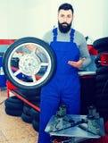 Worker repairing wheel. Young man worker working at restoring wheel in motorcycle workshop Royalty Free Stock Image