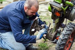 Worker repairs agricultural machine Stock Photos