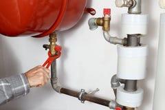 Worker repairs a boiler Stock Image