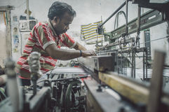Worker repairs machine. VARANASI, INDIA - 21 FEBRUARY 2015: Worker repairs textile machine in small factory. Post-processed with grain, texture and colour effect Royalty Free Stock Photo
