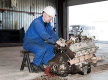 Worker repairs a motor Royalty Free Stock Photo