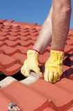 Worker replacing roof tiles on house Stock Photos
