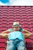 Worker resting on the roof. Working in a hat lying on the roof Royalty Free Stock Photos