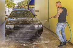 A worker rinses off a black car at the car wash royalty free stock images