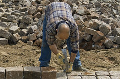 Worker: road builder laying cobblestones Royalty Free Stock Image