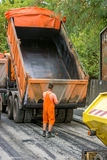 Worker on a road construction. Automatic unloading dump semi trailer with tri-axles during road construction, road construction crew apply the first layer of Stock Image