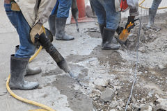 Worker of road construction drilling cement ground Stock Photography
