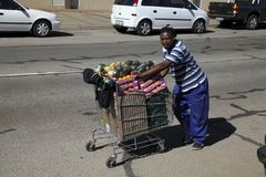 Worker on the road in Potchefstroom. Worker on the road in Potchefstroom with a trolley with fruit on a sunny day Stock Photo