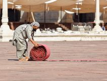 Worker unrolling red carpet in Delhi courtyard. royalty free stock photography